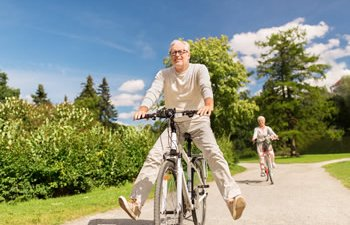An elderly man riding a bicycle
